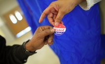 Voting machine operator Robin Coffee-Ruff hands a sticker to a voter who cast his ballot at West Philadelphia High School on U.S. midterm election day morning in Philadelphia, Pennsylvania, November 4, 201