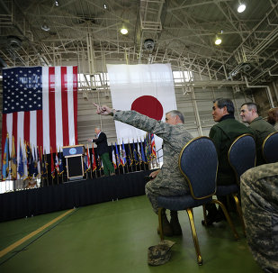 Lt. Gen. Salvatore Angelella, center bottom, the Commander, U.S. Forces Japan, gestures as U.S. Secretary of Defense Chuck Hagel, back left, listens to questions from the U.S. military personnel upon his arrival at the U.S. Yokota Air Base on the outskirts of Tokyo, Saturday, April 5, 2014.