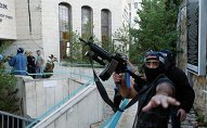 An Israeli police officer gestures as he holds a weapon near the scene of an attack at a Jerusalem synagogue.