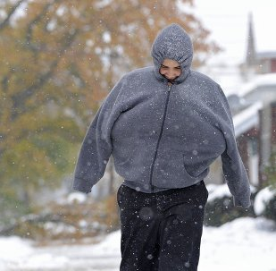 With his arms tucked inside his hooded sweatshirt, Aris Espinosa, 16, of Erie, Pa. walks to school, Tuesday, Nov. 18, 2014 in Erie, Pa. A lake-effect snowstorm dumped up to 4 feet of snow along a stretch of the New York State Thruway on Tuesday