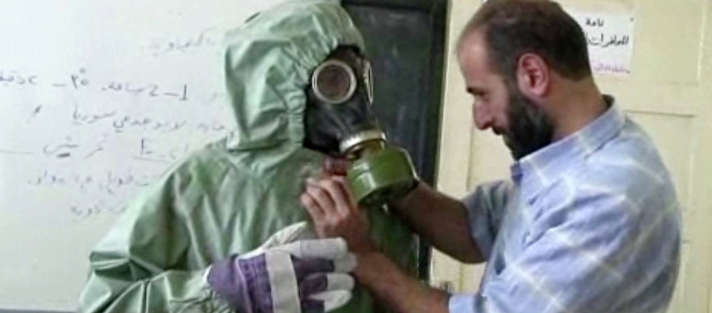 Volunteer adjusting a gas mask and protective suit on a student during a classroom session a on how to respond to a chemical weapons attack in Aleppo, Syria