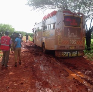 Rescue workers walk near a Nairobi-bound bus that was ambushed outside Mandera town, near Kenya's border with Somalia and Ethiopia, November 22, 2014