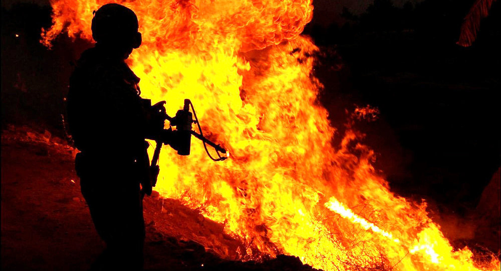 A Soldier uses a flamethrower to ignite a controlled fire near Al Anaflsah, Iraq
