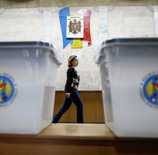Ballot boxes are seen as a member of a local electoral commission passes by at a polling station in Chisinau November 29, 2014