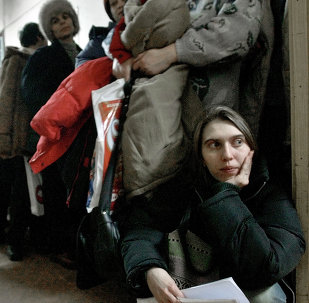 In this image dated Jan.28, 2004, showing a Romanian woman as she leans against the door at the International Office for Migration in Bucharest, Romania, Jan. 28, 2004, waiting in a line to apply for a job in Spain
