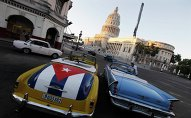 A car with a Cuban flag is parked near Cuban Capitol in Havana December 18, 2014. Cuban President Raul Castro hailed a landmark exchange of prisoners with the United States on Wednesday and praised U.S. President Barack Obama as the two countries agreed to normalize relations after more than five decades of hostility