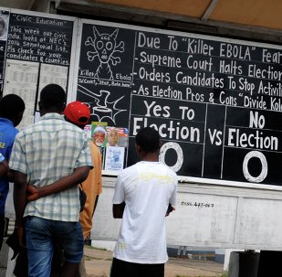 Bystanders read the headlines illustrating the battle over the holding of elections in Liberia amid the Ebola crisis at a street side chalkboard newspaper in Monrovia. (File)