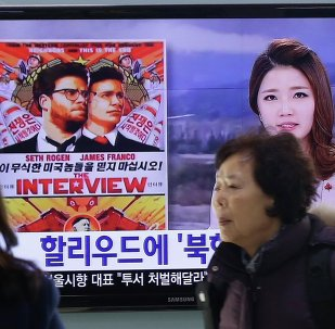 "People walk past a TV screen showing a poster of Sony Picture's ""The Interview"" in a news report, at the Seoul Railway Station in Seoul, South Korea, Monday, Dec. 22, 2014"