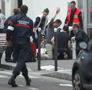 An injured person is treated by nursing staff outside the French satirical newspaper Charlie Hebdo's office, in Paris, Wednesday, Jan. 7, 2015