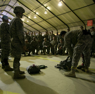 listen to jump master how to prepare their gear for a parachute training exercise in U.S military base Camp Bondsteel, near the village of Sojeve in Kosovo on Sunday, Dec. 21, 2014
