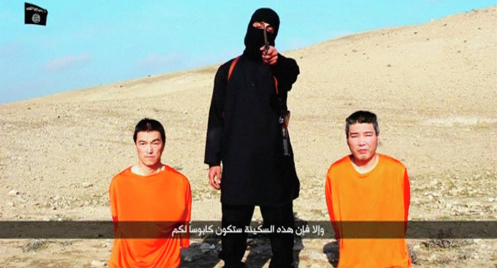 A masked person holding a knife speaks as he stands in between two kneeling men in this still image taken from an online video released by the militant Islamic State group on January 20, 2015