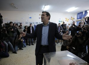 Alexis Tsipras, leader of Greece's Syriza left-wing main opposition party surrounded by photographers reacts as he casts his vote at a polling station in Athens, Sunday, Jan. 25, 2015