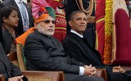 India's Prime Minister Narendra Modi (L) and US President Barack Obama watch India's Republic Day parade in the rain together from their review stand in New Delhi January 26, 2015