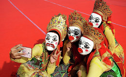 Indonesian Muslim girls take selfie photo during the Mawlid Mask Festival to commemorate the birthday of the Prophet Mohammad on January 25, 2015 in Surabaya, Indonesia