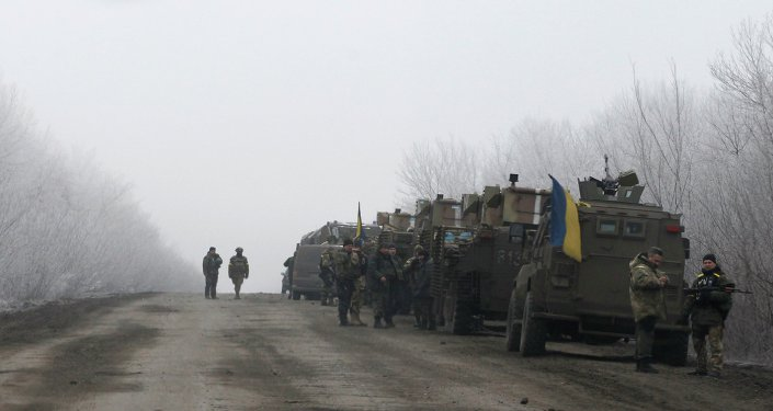Ukrainian military convoy stop on the road between the towns of Dabeltseve and Artemivsk, Ukraine, Saturday, Feb. 14, 2015