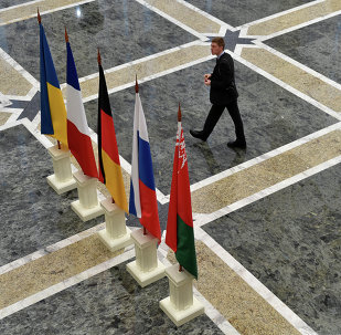 A man walks close to the flags on France, Russia, Germany, Ukraine and Belarus at the presidential residence in Minsk on February 11, 2015