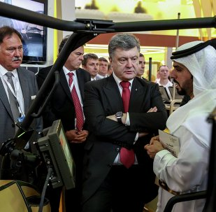 Ukrainian President Petro Poroshenko (2nd R) listens to explanations as he visits the International Defence Exhibition and Conference (IDEX) in Abu Dhabi February 24, 2015