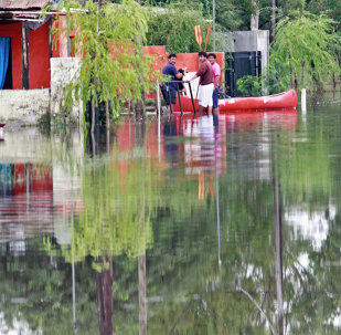 Residents remain near a boat in a flooded street due to heavy rains in Balnearia, Cordoba province, Argentina