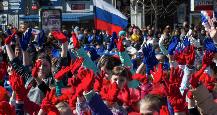 Participants of the Crimean Spring anniversary celebrations march in downtown Simferopol