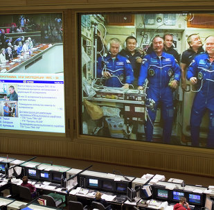 This view from Russian Mission Control Center shows live television of the Expedition 39 crew members gathered together on the International Space Station.