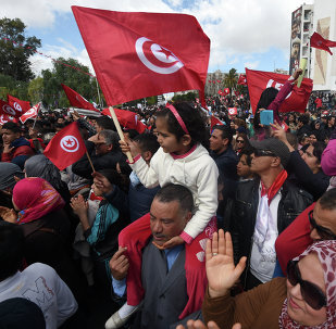 Tunisians wave their national flag and chant slogans during a march against extremism outside Tunis' Bardo Museum on March 29, 2015
