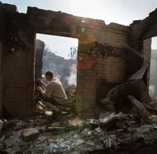 A journalist films a destroyed house following a mortar attack in Semyonovka village, outside Slavyansk, Ukraine, Friday, May 23, 2014