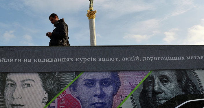 A man stands next to an advertising placard showing British pounds, US dollars and Ukrainian hryvnia banknotes in the Ukrainian capital Kiev