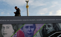 A man stands next to an advertising placard showing British pounds, US dollars and Ukrainian hryvnia banknotes in the Ukrainian capital Kiev.