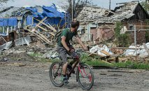 A local citizen rides a bicycle past destroyed houses after heavy fighting between independence supporters and Ukrainian government troops just outside Slavyansk, eastern Ukraine, Wednesday, July 9, 2014