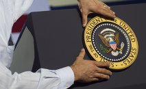 An aide places the Presidential seal on the podium prior to US President Barack Obama speaking during a campaign event at Kissimmee Civic Center in Kissimmee, Florida