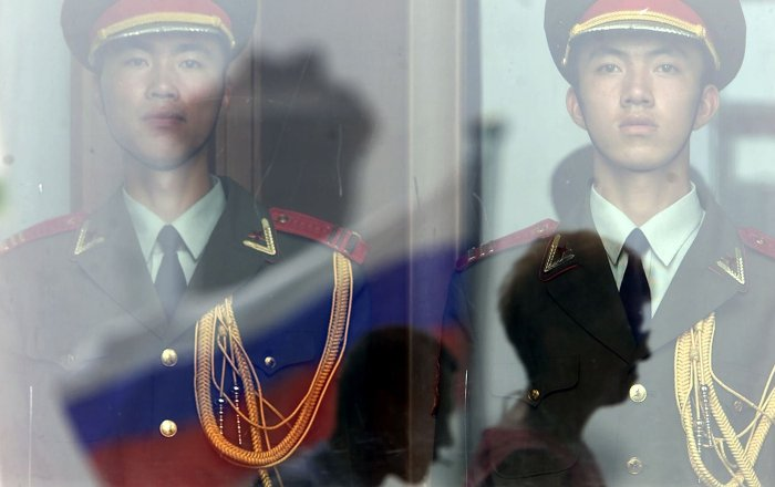 Chinese People's Liberation Army soldiers stand guard inside the Great Hall of the People as the Russian flag flies on Tiananmen Square