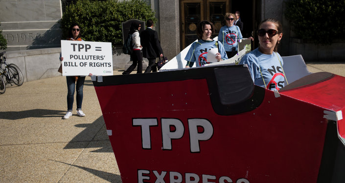 People protesting the TPP look at other protesters, as they rally to advocate for an increase in pay to $15 USD per hour, as part of a Fight for $15 labor effort on Capitol Hill April 22, 2015 in Washington