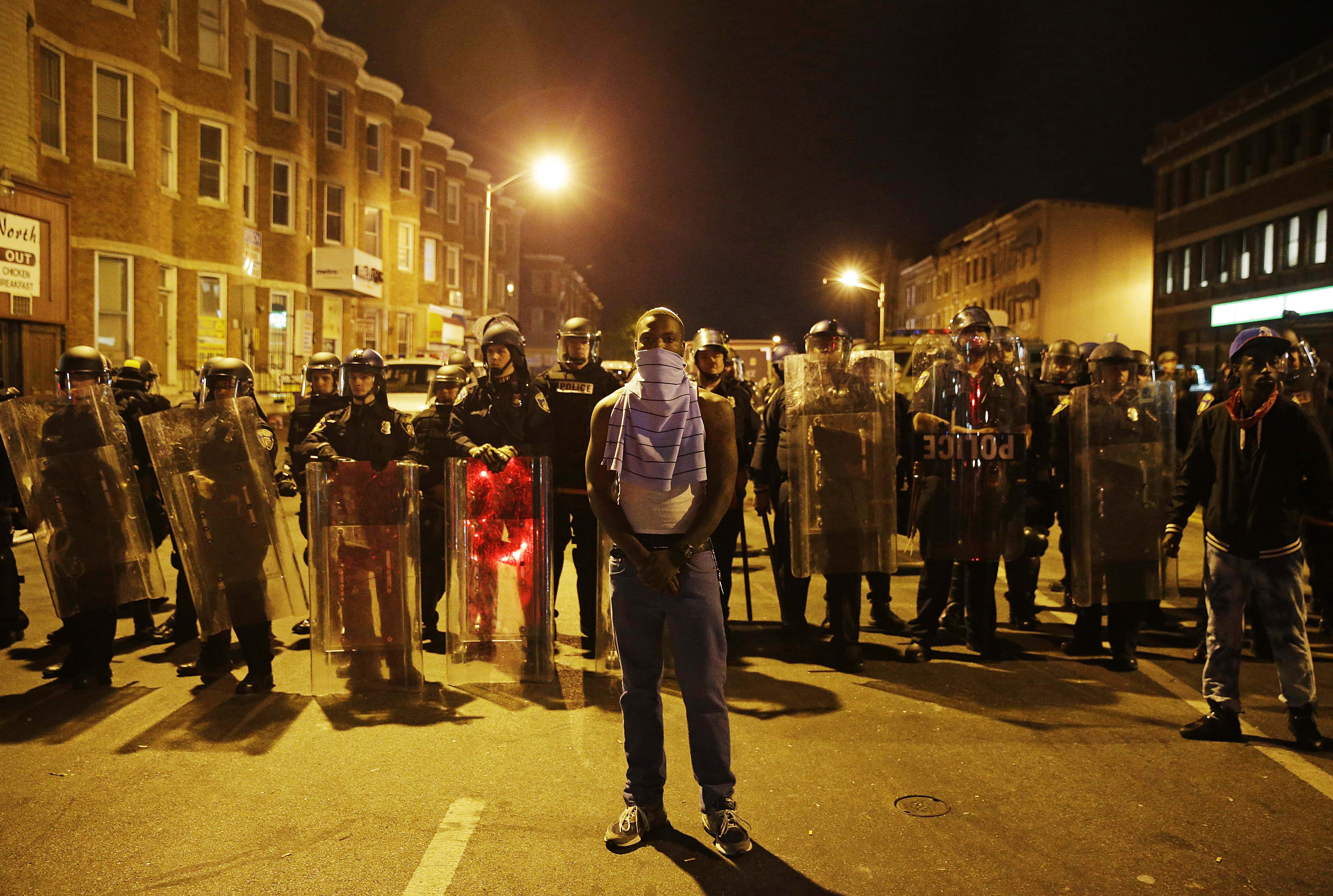 A man stands in front of a line of police officers in riot gear as part of a community effort to disperse the crowd ahead of a 10 p.m. curfew in the wake of Monday's riots following the funeral for Freddie Gray, Tuesday, April 28, 2015, in Baltimore.