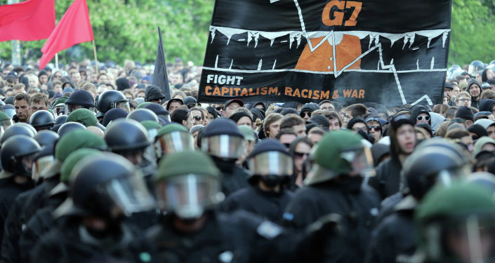 Protesters hold a banner reading ' Stop G7 - Fight Capitalism, Racism and War' as they take part in the 'Revolutionary' May Day demonstration in Berlin's Kreuzberg district on May 1, 2015