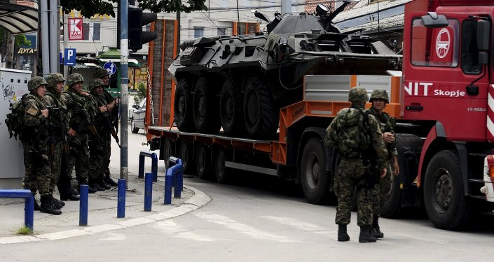 A truck loaded with a damaged armored police vehicle passes near police check point in Kumanovo, Macedonia