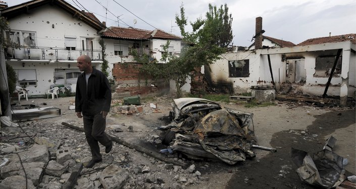 A man walks through a damaged house in Kumanovo, Macedonia May 11, 2015