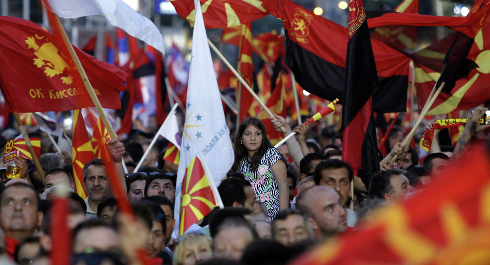 Supporters of the ruling coalition wave national and party flags, during a rally in front of the Parliament building in Skopje, Macedonia, Monday, May 18, 2015