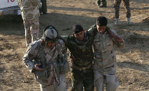 Iraqi soldiers help a wounded comrade in the area of Sayed Ghareeb, near Dujail, some 70 kilometres north of Baghdad