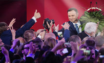 Andrzej Duda (R), presidential candidate of Law and Justice (PiS) right wing opposition party celebrates after the announcement of the exit poll results of the second round of the presidential election in Warsaw, on May 24, 2015