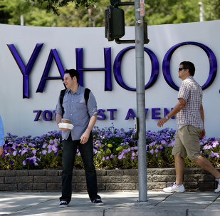 People walk in front of a Yahoo sign at the company's headquarters in Sunnyvale, California.