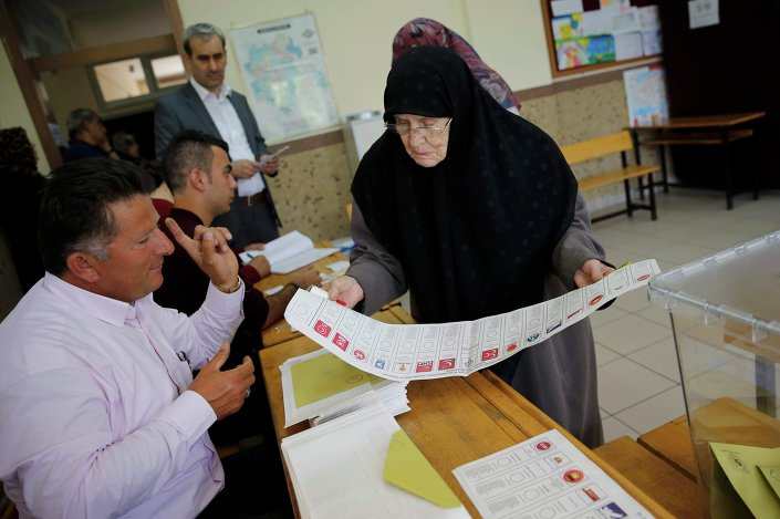 A woman looks at a ballot paper at a polling station during the parliamentary election in Konya, Turkey, June 7, 2015.