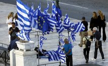 A street vendor sells Greek and EU flags before an upcoming demonstration by Greeks calling on the government to clinch a deal with its international creditors and secure Greece's future in the Eurozone in Athens, Greece, June 22, 2015