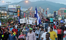 Protesters march to the Presidential House to demand the resignation of Honduras' President Juan Orlando Hernandez, in Tegucigalpa, Honduras, Friday, July 3, 2015