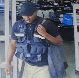 CCTV image of a man who posed as an armored car guard letting him carry $75,000 out from a Walmart
