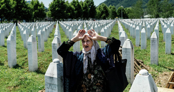 An elderly Bosnian woman reacts at the grave of her relative at the Potocari Memorial Center near the eastern Bosnian town of Srebrenica on July 10, 2015