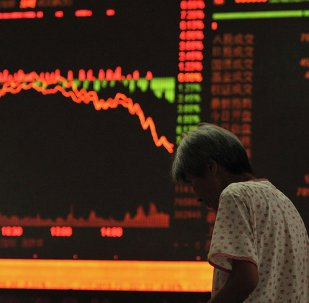An investor stands in front of an electronic board showing stock information at a brokerage house in Fuyang, Anhui province, July 27, 2015