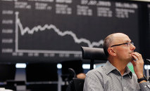 A trader watches his screens at the stock market in Frankfurt, Germany