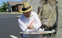 Mark Balma works on a mural of Cecil the lion outside Dr. Walter James Palmer's dental office in Bloomington, Minnesota.