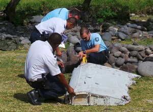French gendarmes and police inspect a large piece of plane debris which was found on the beach in Saint-Andre.
