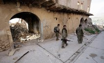 In this Thursday Jan. 29, 2015 photo, fighters of the Turkey-based Kurdish Workers' Party (PKK) walk in the damaged streets of Sinjar, Iraq